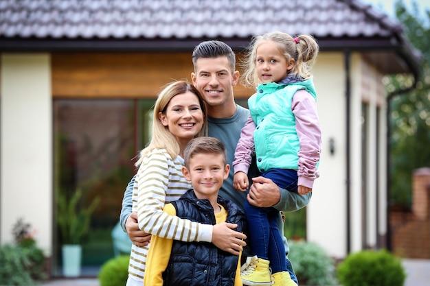 Famille heureuse dans la cour près de leur maison