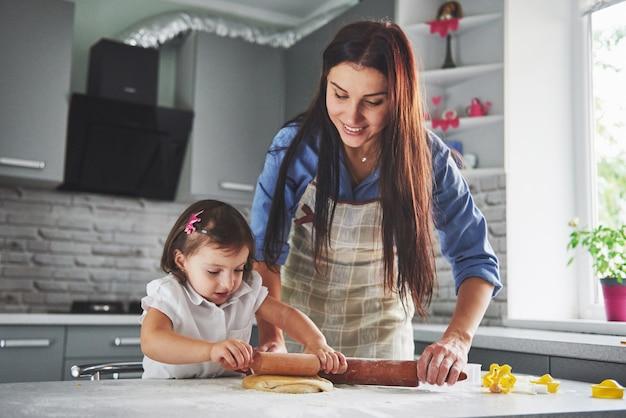 Famille heureuse dans la cuisine. concept de nourriture de vacances. mère et fille préparent la pâte, préparent des biscuits. famille heureuse en faisant des cookies à la maison. nourriture maison et petit assistant