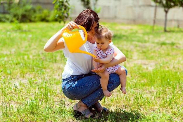 Famille heureuse dans le jardin. l'eau d'un arrosoir est versée dans les mains de l'enfant. mère lave ses mains à un enfant dans le jardin d'un arrosoir jaune.