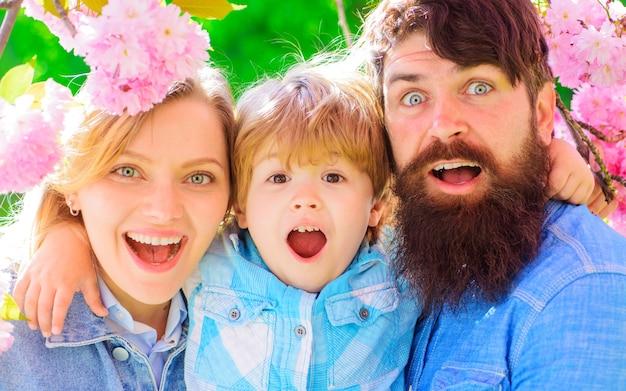 Famille heureuse dans le jardin de printemps. mère père avec petit fils ensemble en sakura en fleurs. couple heureux dans le parc de sakura.
