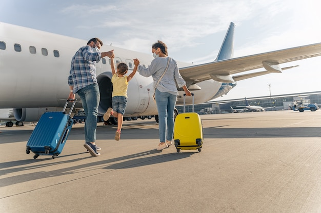 Famille heureuse dans des masques appréciant voyager ensemble