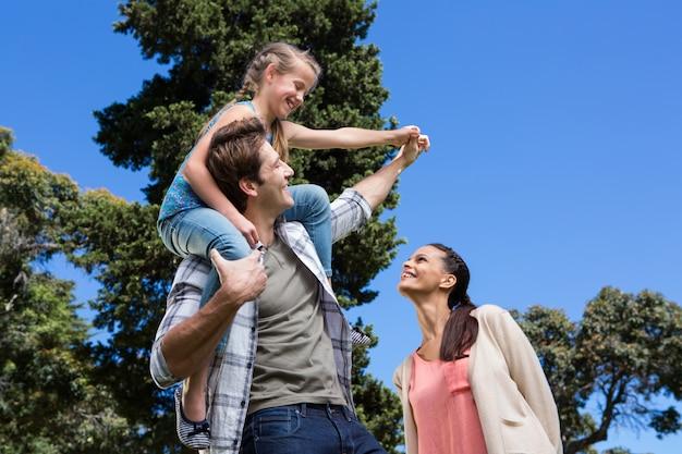 Famille heureuse dans le parc ensemble