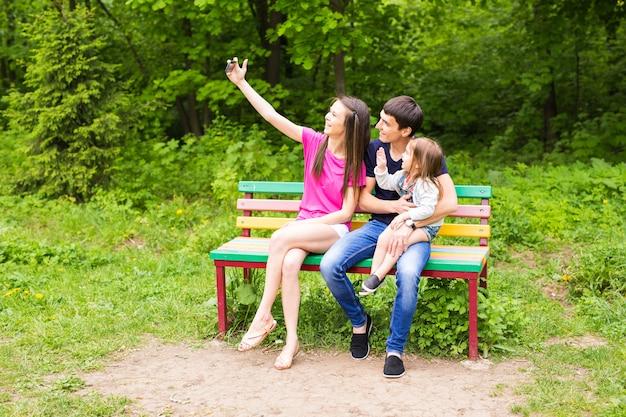 Famille heureuse dans le parc prenant selfie sur une journée ensoleillée