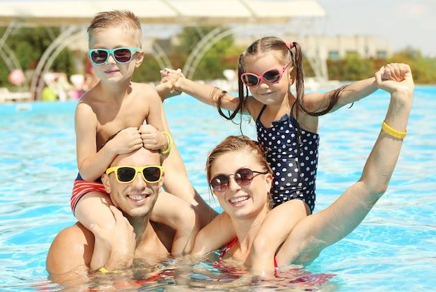 Famille heureuse dans la piscine du parc aquatique