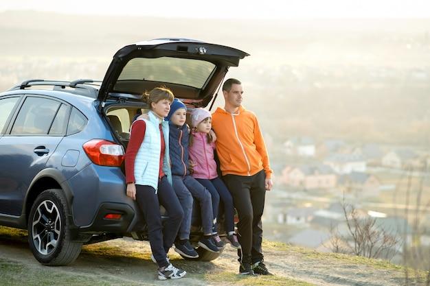 Famille heureuse, debout, ensemble, près, a, voiture, à, coffre ouvert, apprécier, vue