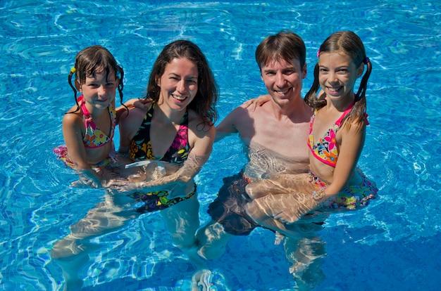 Famille heureuse avec deux enfants dans la piscine. les parents et les enfants souriants en vacances d'été nagent et s'amusent. sport en famille, vacances actives et saines