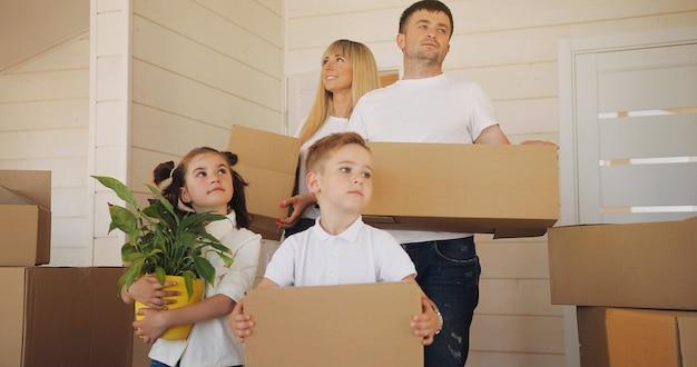 Famille heureuse avec deux enfants à la nouvelle maison. mère père et enfant dans une nouvelle maison