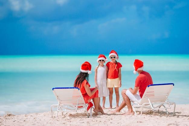 Famille heureuse avec deux enfants à santa hat en vacances d'été