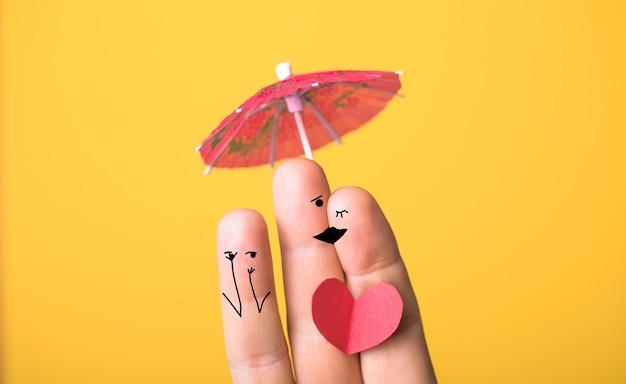 Une famille heureuse de doigt amoureuse de coeur sous le parapluie