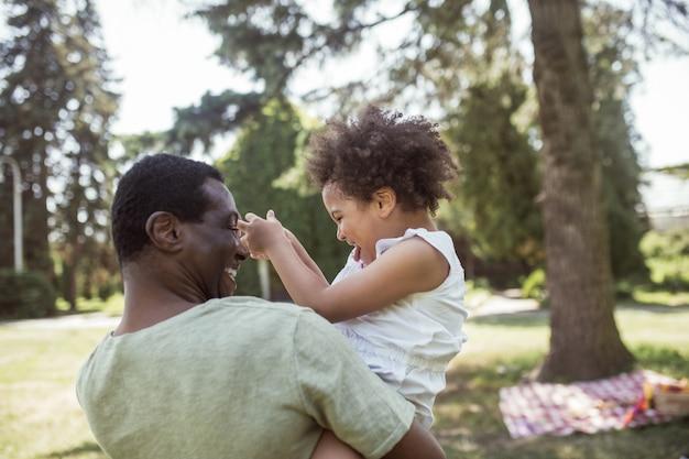 Famille heureuse. doux enfant bouclé assis jouant avec son père et se sentant heureux
