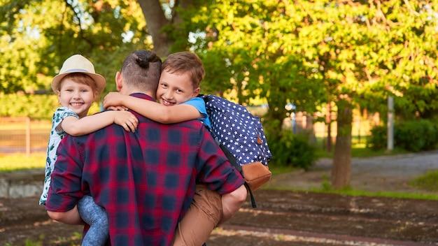 Famille heureuse du père et des enfants.le père tient les enfants dans ses bras