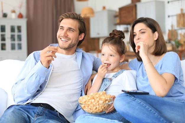 Famille heureuse avec un enfant assis sur un canapé en train de regarder la télévision et de manger du pop-corn, de jeunes parents embrassant leur fille se relaxant sur un canapé ensemble.