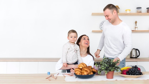 Famille heureuse avec enfant dans la cuisine et l'espace de copie
