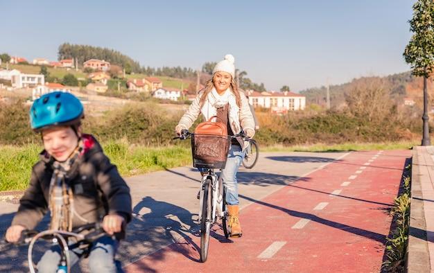 Famille heureuse avec un enfant faisant du vélo par la nature par une journée d'hiver ensoleillée