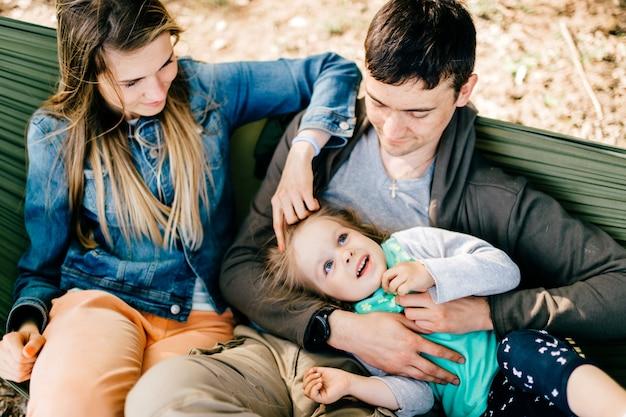 Famille heureuse avec enfant se détendre dans un hamac en plein air.