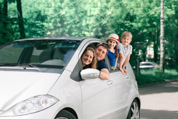 Famille heureuse avec enfants assis dans une voiture familiale