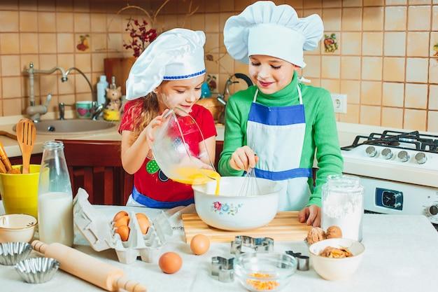 Famille heureuse, des enfants drôles préparent la pâte, préparent des biscuits dans la cuisine