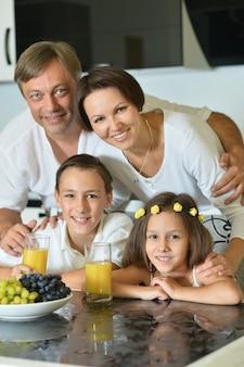 Famille heureuse avec des enfants mangeant à table