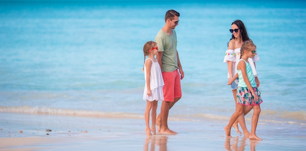 Famille heureuse avec enfants marcher sur la plage au coucher du soleil