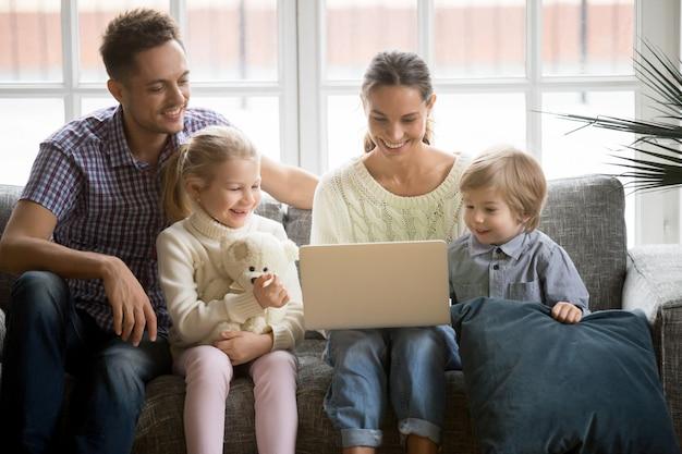 Famille heureuse avec des enfants s'amusant à l'aide d'un ordinateur portable sur un canapé