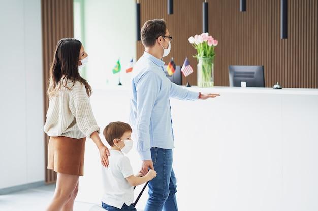 Famille heureuse enregistrement à l'hôtel