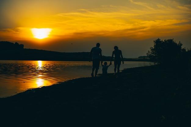Famille heureuse ensemble, les parents avec leur petit enfant au coucher du soleil. père élevant bébé dans l'air.