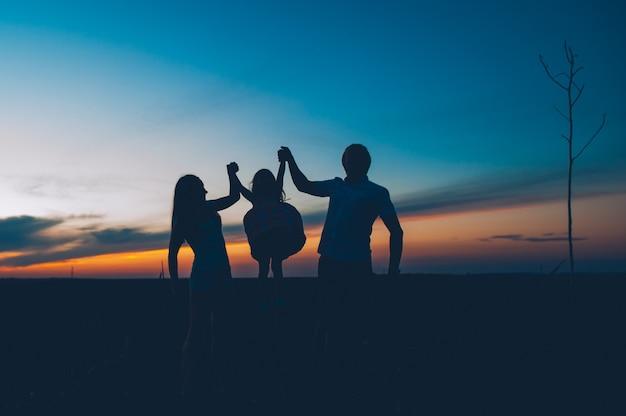 Famille heureuse ensemble, les parents avec leur petit enfant au coucher du soleil. père élevant bébé dans les airs.