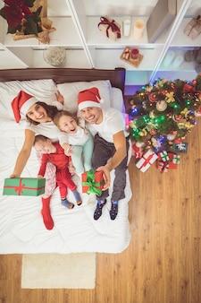 La famille heureuse est assise dans un lit avec des cadeaux. vue d'en-haut
