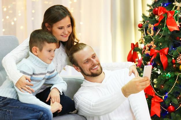 Famille heureuse faisant une photo dans le salon de vacances à la maison
