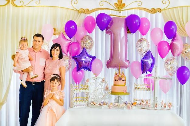 Une famille heureuse fête son anniversaire dans le restaurant près du bar à bonbons de luxe dans des tons violets.