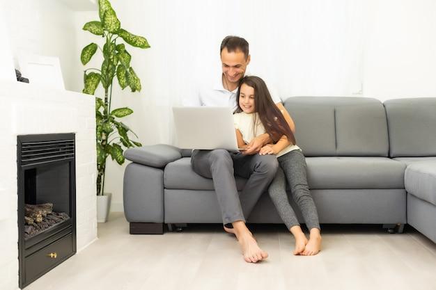 Famille heureuse avec une fillette s'amusant à l'aide d'un ordinateur portable assis sur un canapé, des parents et une fille enfant riant se détendre à la maison avec un ordinateur en regardant une vidéo internet amusante, en passant un appel en ligne