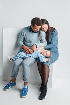 Une famille heureuse d'homme afro et femme caucasienne et enfant sur studio blanc