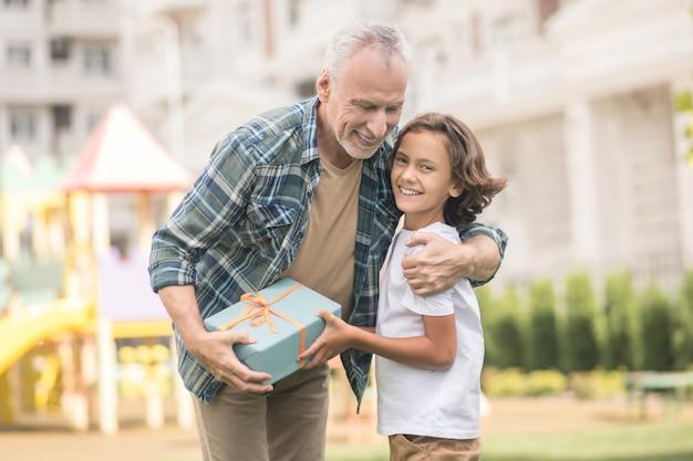 Famille heureuse. homme aux cheveux gris tenant une boîte-cadeau et étreignant son fils