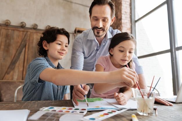 Famille heureuse inspirée étant concentrée sur la peinture d'une image à l'aquarelle avec des enfants lavant des pinceaux et papa appliquant des traits