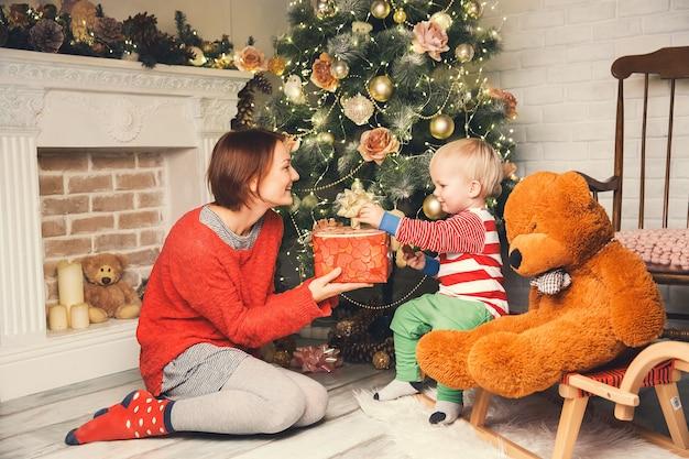 Famille heureuse à l'intérieur d'une maison sur fond d'arbre de noël avec des cadeaux