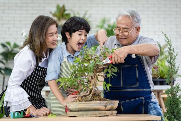 Famille heureuse jardinant ensemble dans le jardin, grand-père petit-fils et femme prenant soin de la nature