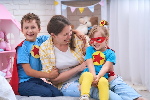 Famille heureuse. une jeune femme joue avec ses enfants dans des super-héros.