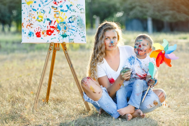 Famille heureuse. jeune jolie mère s'amuser avec ses enfants à l'extérieur. peinture de famille