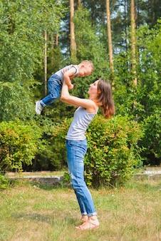 Famille heureuse. jeune maman lève bébé par journée ensoleillée. émotions humaines positives, sentiments, joie