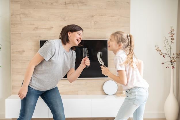 Famille heureuse jeune mère adulte et jolie fille adolescente s'amusant chanter une chanson de karaoké dans des brosses à cheveux.