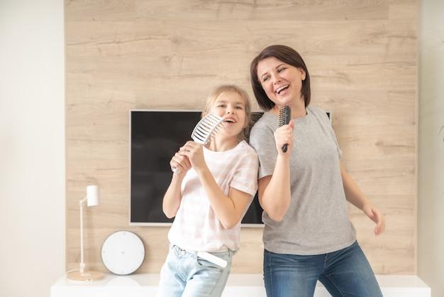 Famille heureuse jeune mère adulte et jolie fille adolescente s'amusant chanter une chanson de karaoké dans des brosses à cheveux