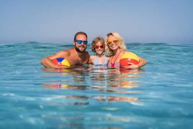Famille heureuse jouant dans la mer mère et père de l'enfant s'amusant pendant les vacances d'été concept de mode de vie sain et actif