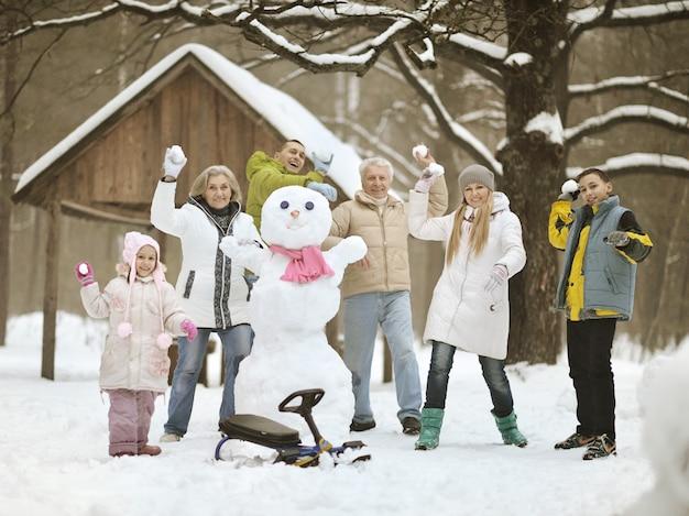 Famille heureuse jouant dans la neige fraîche et construisant un bonhomme de neige lors d'une belle journée d'hiver ensoleillée en plein air dans la nature