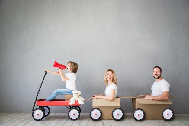 Famille heureuse jouant dans la nouvelle maison père mère et enfant s'amusant ensemble jour du déménagement