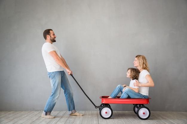 Famille heureuse jouant dans la nouvelle maison père mère et enfant s'amusant ensemble le jour du déménagement