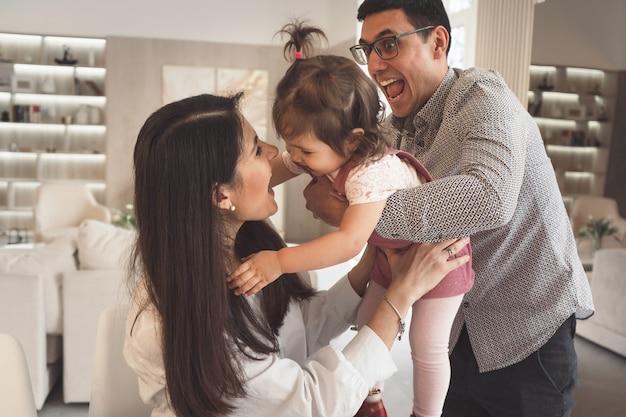 Une famille heureuse joue avec sa fille. papa jette le bébé