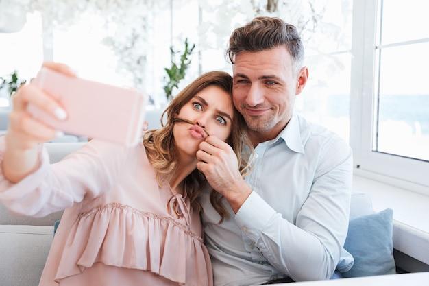 Famille heureuse de joyeux couple marié faisant selfie et s'amuser ensemble, tout en ayant rendez-vous dans un café de la ville confortable