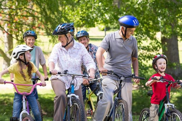 Famille heureuse sur leur vélo au parc