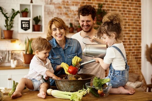 Famille heureuse avec leurs enfants cuisinant dans la cuisine