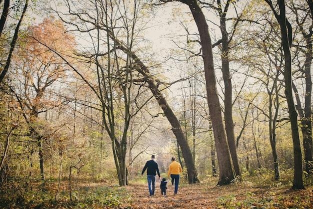 Famille heureuse et leurs fils se promènent dans le parc de l'automne et passent un bon moment. famille se reposant dans le magnifique parc d'automne.
